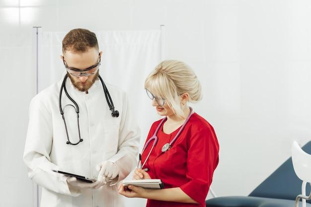 Ärzte in uniform, mann und frau in einem gynäkologischen büro.