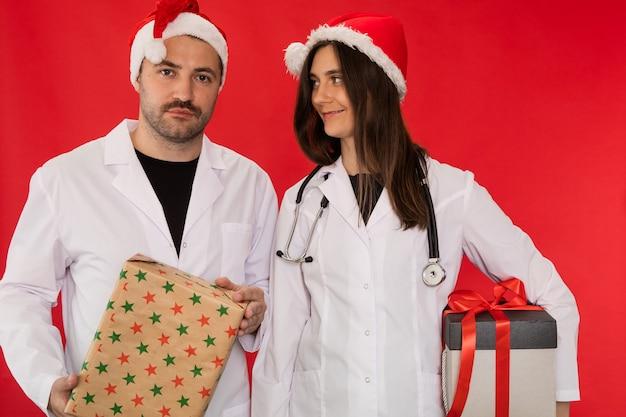 Ärzte in weihnachtsmannhüten halten weihnachtsgeschenkboxen