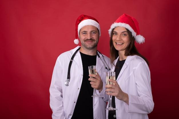 Ärzte in weihnachtsmannhüten jubeln mit champagnergläsern