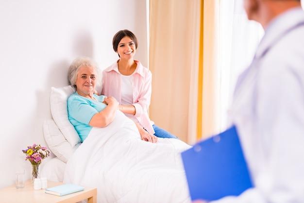 Ärzte kümmern sich um eine alte frau in einer klinik.