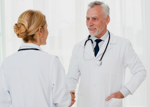 Ärzte lächeln und händeschütteln