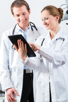 Ärzte - männer und frauen - diskutieren testberichte, die auf ihrem tablet-computer angezeigt werden