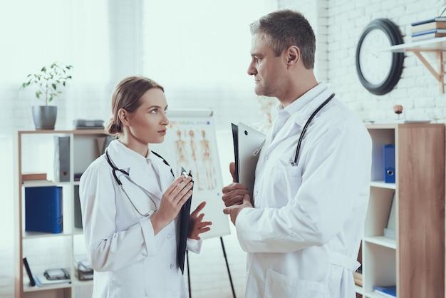 Ärzte mit stethoskopen in weißen gewändern sprechen