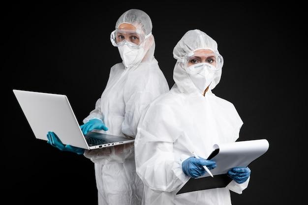 Ärzte posieren beim tragen von schutzkleidung