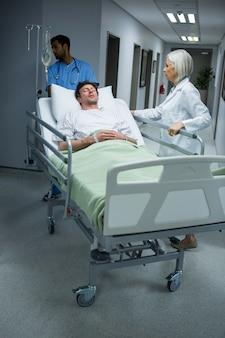 Ärzte schieben notbahre bett im korridor