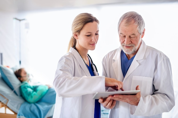 Ärzte und ärztinnen mit tablet sprechen im krankenhaus, coronavirus-konzept.