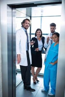 Ärzte und geschäftsfrau stehen im aufzug