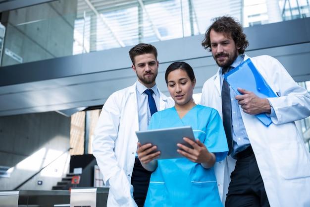 Ärzte und krankenschwester betrachten digitale tablette