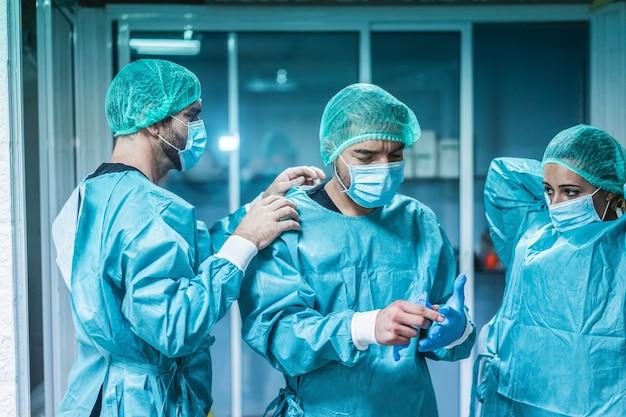 Ärzte und krankenschwester, die sich darauf vorbereiten, während des ausbruchs der coronavirus-pandemie im krankenhaus für eine chirurgische operation zu arbeiten - fokus auf der linken hand
