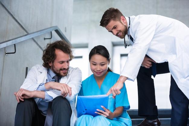 Ärzte und krankenschwester diskutieren über einen bericht
