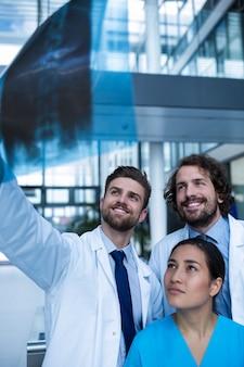 Ärzte und krankenschwester untersuchen röntgenbericht