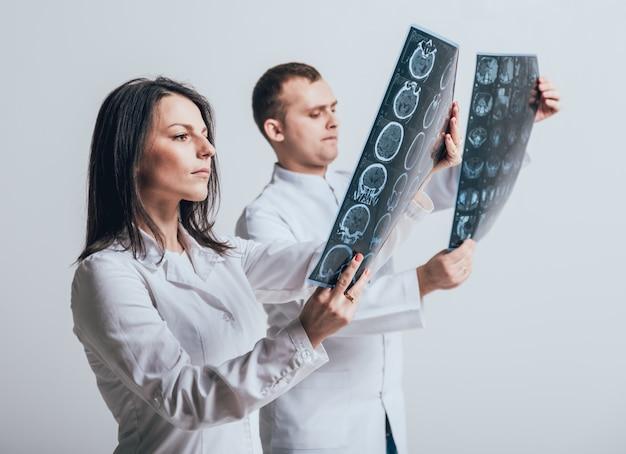 Ärzte untersuchen aufmerksam den mrt-scan des patienten.