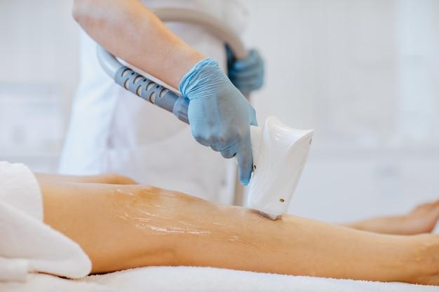 Ärztehände in blauen medizinischen handschuhen halten eine enthaarungsmaschine und benutzen sie an den beinen der frau.
