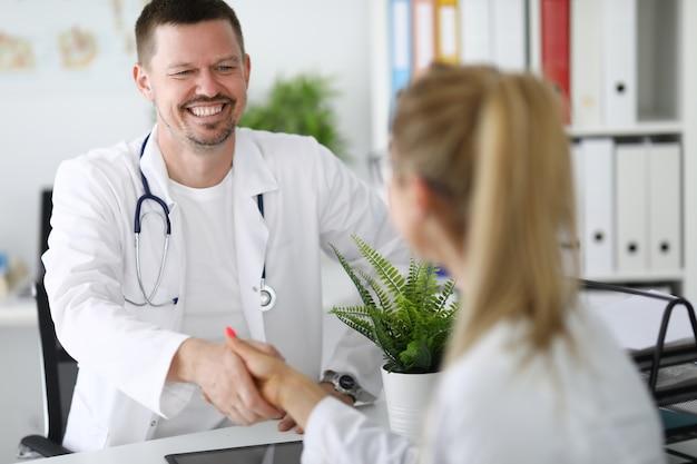 Ärztekollegen lächeln und geben sich im büro die hand