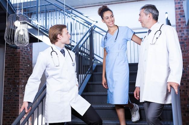 Ärzteteam, das auf treppenhaus im krankenhaus auf einander einwirkt