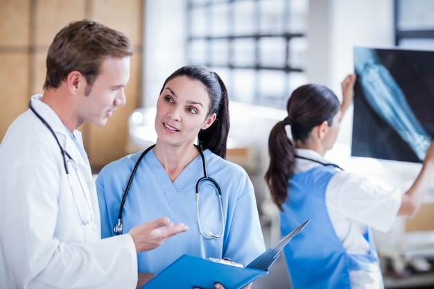 Ärzteteam, das den bericht über klemmbrett am krankenhaus bespricht