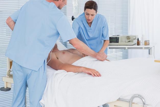 Ärzteteam, das einen mann mit einem defibrillator wiederbelebt