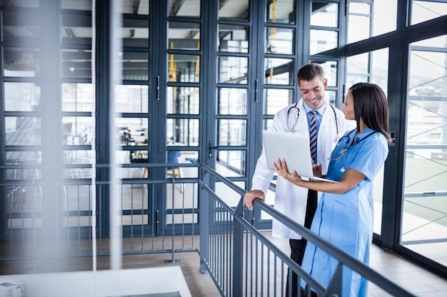 Ärzteteam, das laptop im krankenhaus betrachtet