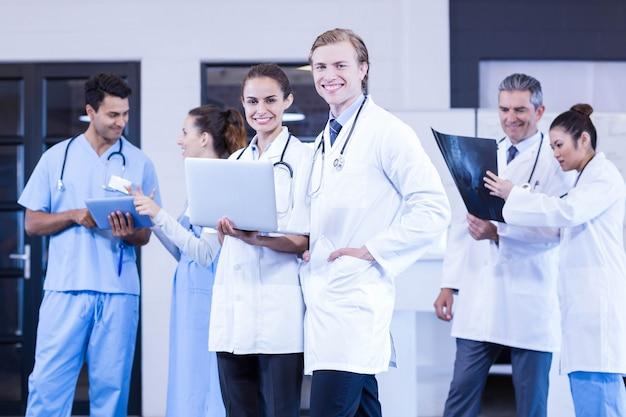 Ärzteteam, das röntgenstrahlbericht bespricht und laptop und digitale tablette im krankenhaus verwendet