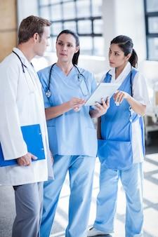 Ärzteteam, das tabletten-pc in der halle betrachtet