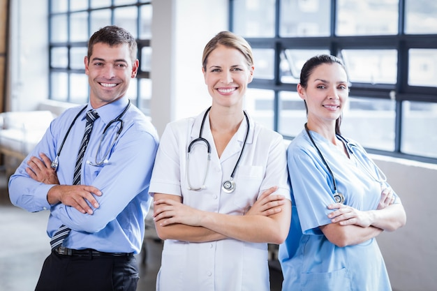 Ärzteteam, das zusammen an der kamera am krankenhaus lächelt