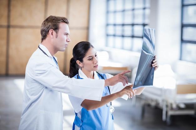 Ärzteteam, das zusammen röntgenstrahl krankenhaus betrachtet
