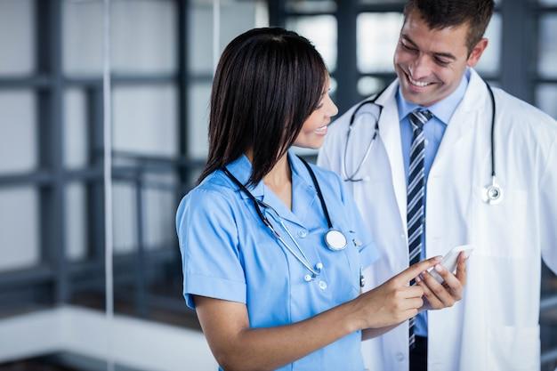 Ärzteteam, das zusammen telefon im krankenhaus betrachtet