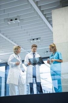 Ärzteteam diskutiert über röntgenbericht im korridor