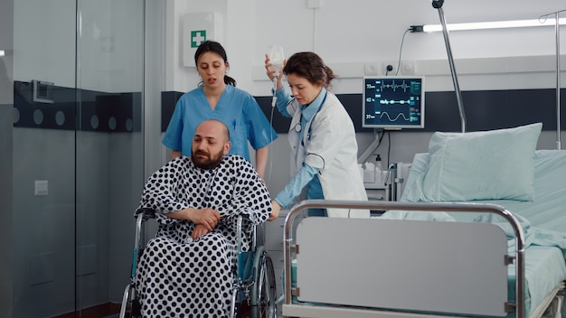 Ärzteteam hilft kranken patienten mit beinfraktur beim einsetzen in den rollstuhl