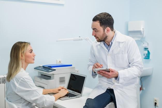 Ärzteteam mit dem tabletten-pc, der am krankenhaus steht und spricht