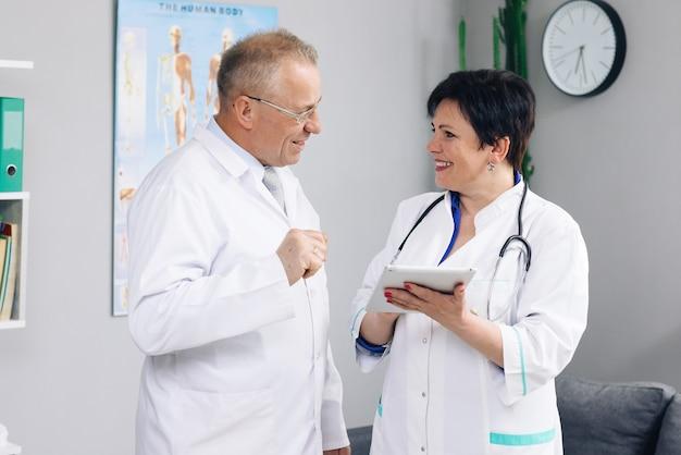Ärzteteam zwei alte männliche und junge ärztinnen tragen weiße kittel, sprechen, verwenden digitales tablet