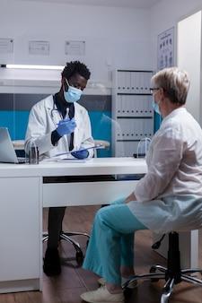 Ärztin afrikanischer abstammung, die notizen auf papieren zur konsultation macht