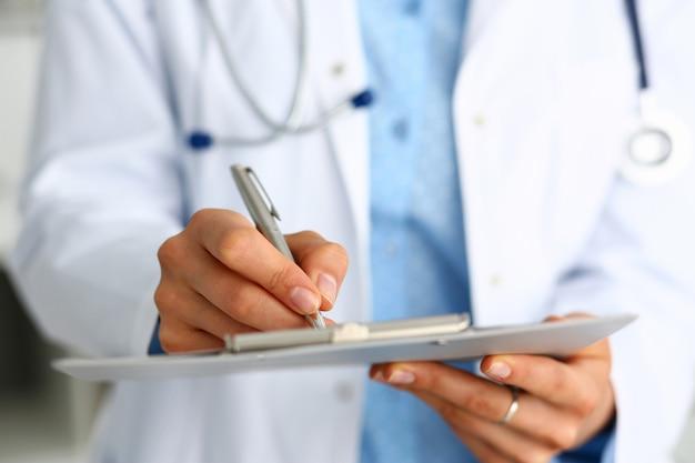 Ärztin arm halten silbernen stift und block