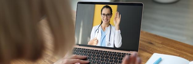 Ärztin auf laptop-bildschirm winkt hand zu krankem patienten