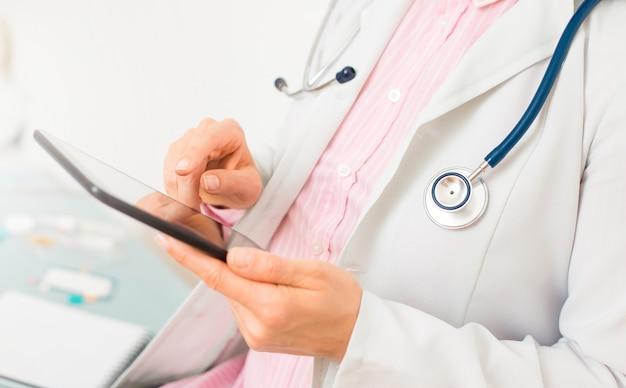 Ärztin benutzt tablette für arbeit. nahansicht.
