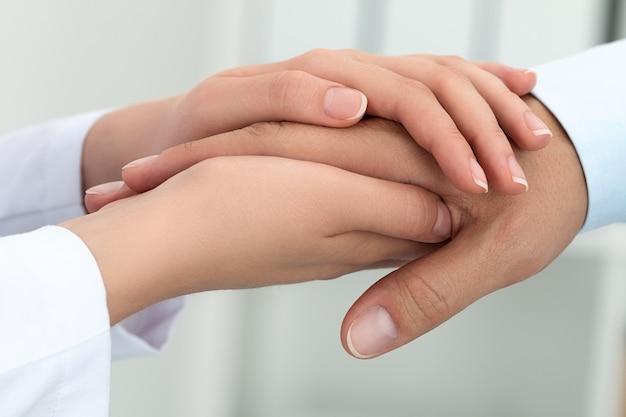 Ärztin beruhigt ihre patientin. hände nahaufnahme. gesundheitswesen und medizinisches konzept.