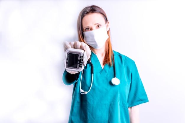 Ärztin chirurgin mit maske und stethoskop mit blick auf ein blutdruckmessgerät-konzept bluthochdruck muss die herzkrankheit des krankenhauses besuchen