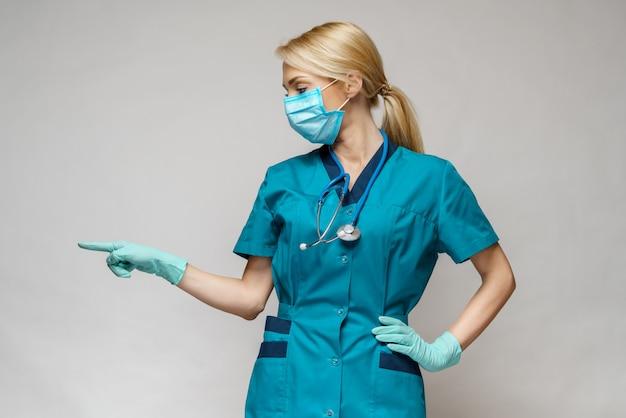 Ärztin der krankenschwester mit schutzmaske und latexhandschuhen - zeigt auf virtueller liste