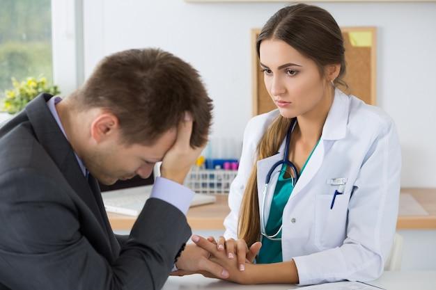 Ärztin der medizin, die geschäftsmannhand für ermutigung hält, die ihm schlechte nachrichten erzählt. sofortiger relativer verlust, stress, kopfschmerzen und medizinisches servicekonzept