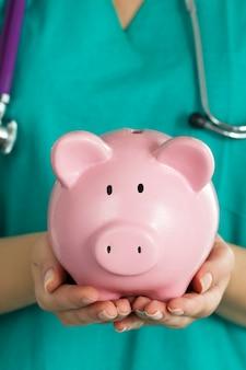 Ärztin der medizin, die grüne uniform trägt, die lustiges rosa sparschwein hält. doktor hände schließen