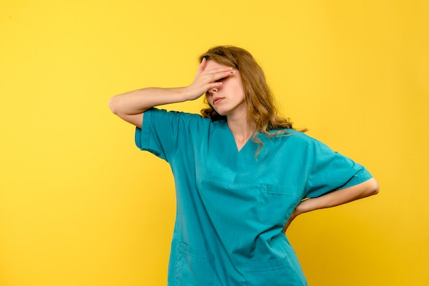 Ärztin der vorderansicht betont auf gelbem raum