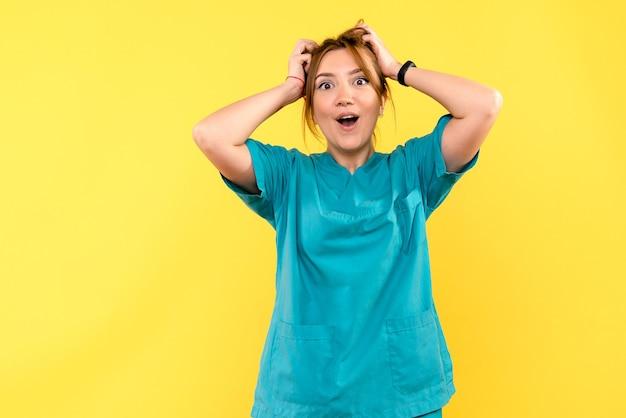 Ärztin der vorderansicht, die auf gelbem raum aufgeregt fühlt