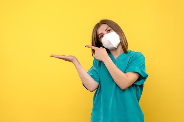Ärztin der vorderansicht, die auf gelbem raum aufwirft