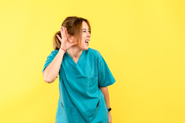 Ärztin der vorderansicht, die auf gelbem raum hört