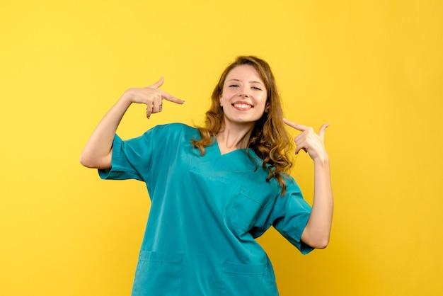 Ärztin der vorderansicht, die auf gelbem raum lächelt