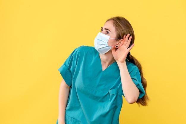 Ärztin der vorderansicht, die auf kovidpandemie des gelben hintergrundgesundheitskrankenhauses hört