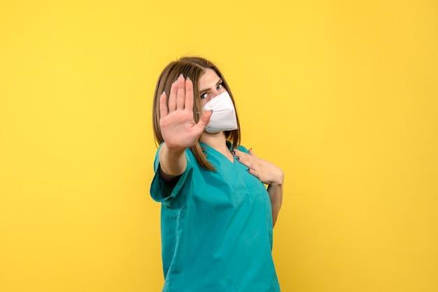 Ärztin der vorderansicht, die bittet, auf gelbem raum anzuhalten