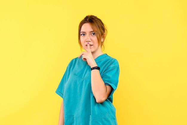 Ärztin der vorderansicht, die bittet, auf gelbem raum ruhig zu sein