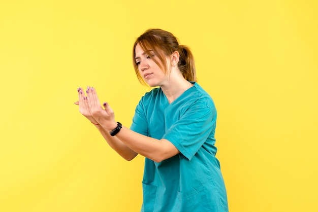 Ärztin der vorderansicht, die das lesen auf gelbem raum nachahmt