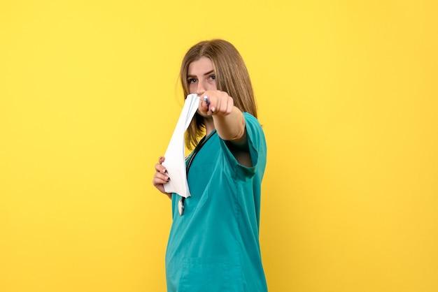 Ärztin der vorderansicht, die dateien auf gelbem raum hält